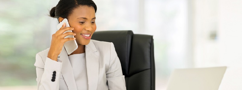 cheerful african american businesswoman talking on cell phone in the office