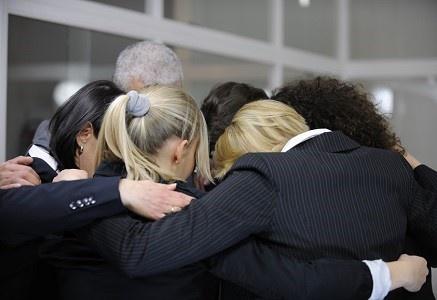 Team building event: businessmen in 'group hug' in office